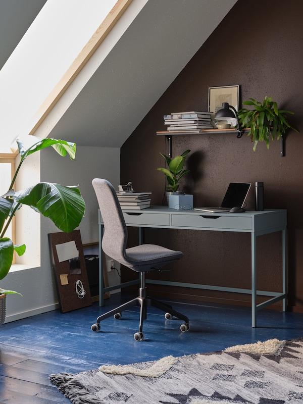 مساحة عمل بها نباتات، ورف بمصباح ضوء موضعي، ومكتب ALEX وكرسي مكتب LÅNGFJÄLL رمادي داكن/أسود.