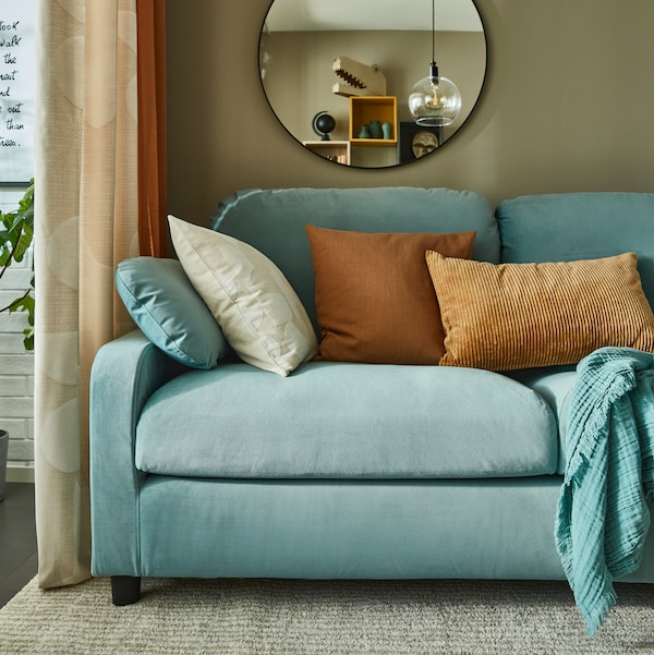A 3-seat sofa with chaise longue, a white shelving unit with doors, a knitted/multicolour blanket, cushions.