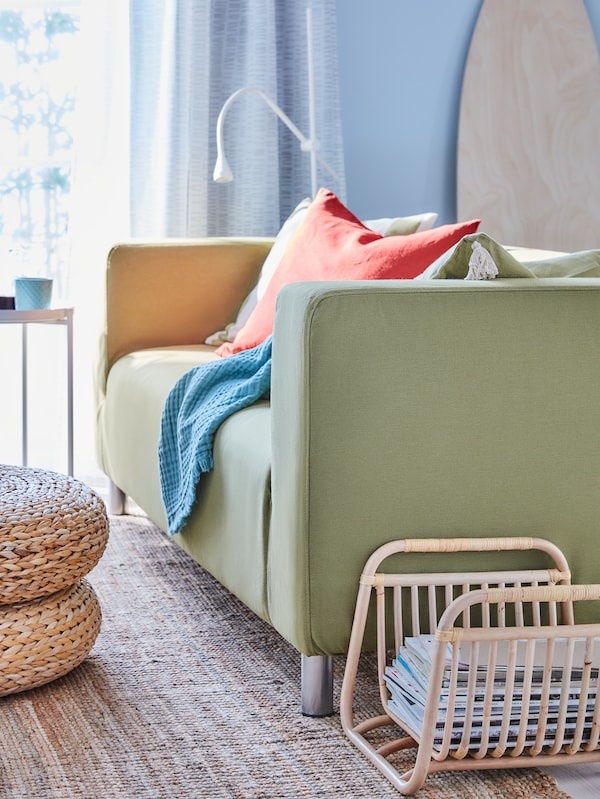 A yellow-green sofa with brightly-coloured cushions and a throw on a rug next to a bamboo magazine stand.