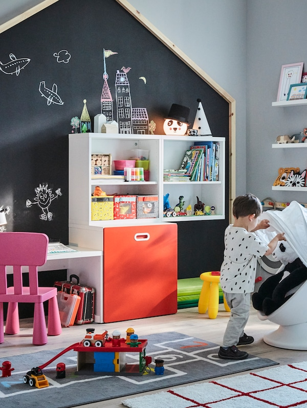 A child standing at an IKEA PS LÖMSK chair with a soft toy in it, by a STUVA/FRITIDS table with toy storage with a red door.
