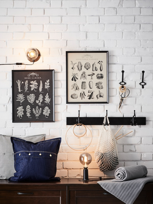 A white brick wall with pictures in picture frames, lighting, hooks for hanging and a cabinet top holding various items.
