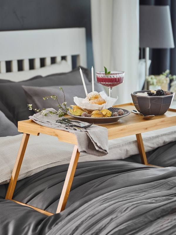 Un plateau de lit RESGODS en bambou contenant un somptueux petit-déjeuner repose sur la literie blanche et grise d'un lit IDANÄS.