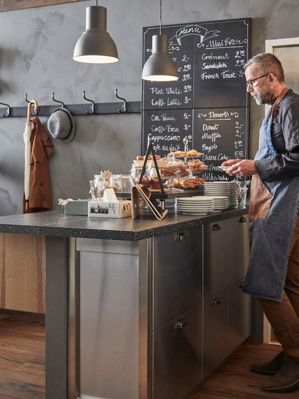 Muž v zástere stojí pred čiernou pracovnou doskou SÄLJAN s minerálovým vzorom, za ním tabuľa s ručne napísaným menu.