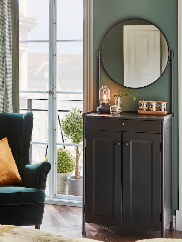 Une armoire KORNSJÖ contre un mur avec un miroir sur des supports. Une lampe de table, un vase et des pots en verre avec couvercles sont sur le dessus.