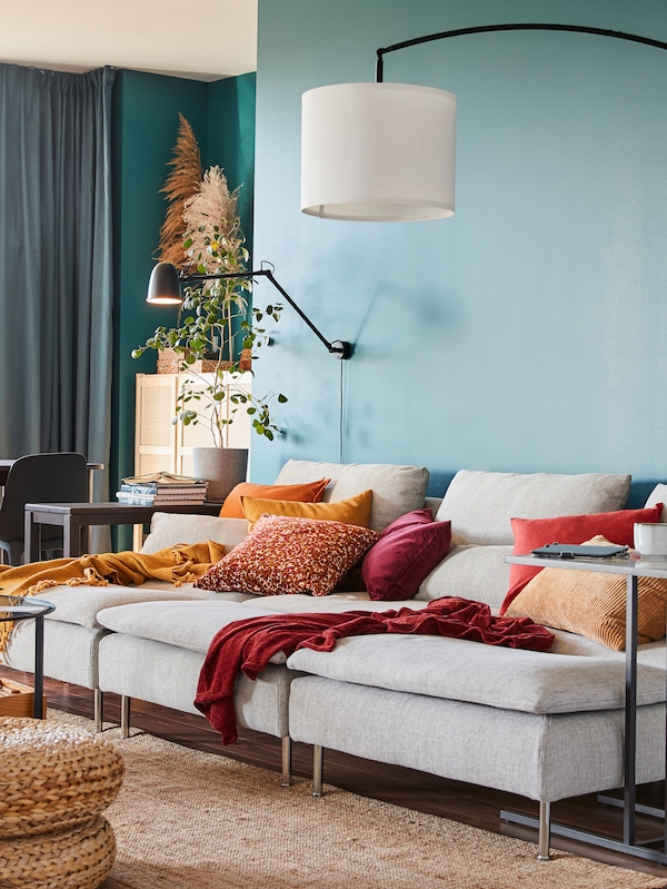 Trois méridiennes beiges/brunes assemblées en un généreux canapé, un tapis en jute, un lampadaire avec arceau et des coussins rouges/jaunes.