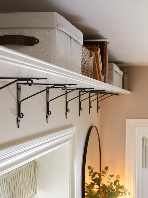 A long shelf near the ceiling above two mirrors with storage boxes.