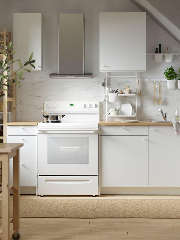 مطبخ أبيض صغير بخزائن قاعدة بيضاء وخزائن حائط بيضاء ولوح حائط بمظهر الرخام الأبيض وفرن.