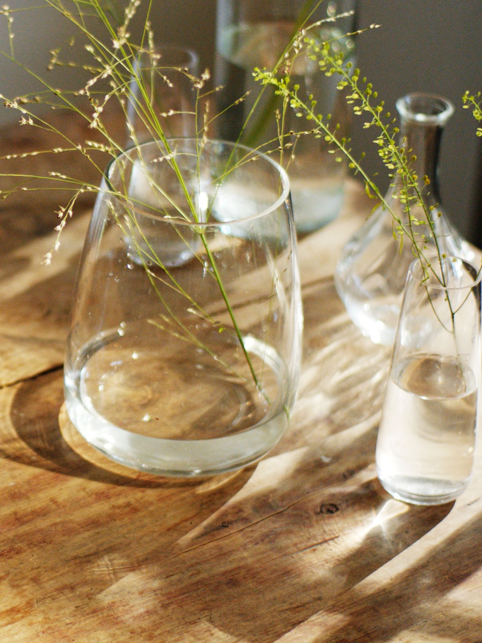 A wooden table holds a group of mixed clear glass vases, including a curved BERÄKNA clear glass vase with a plant sprig.