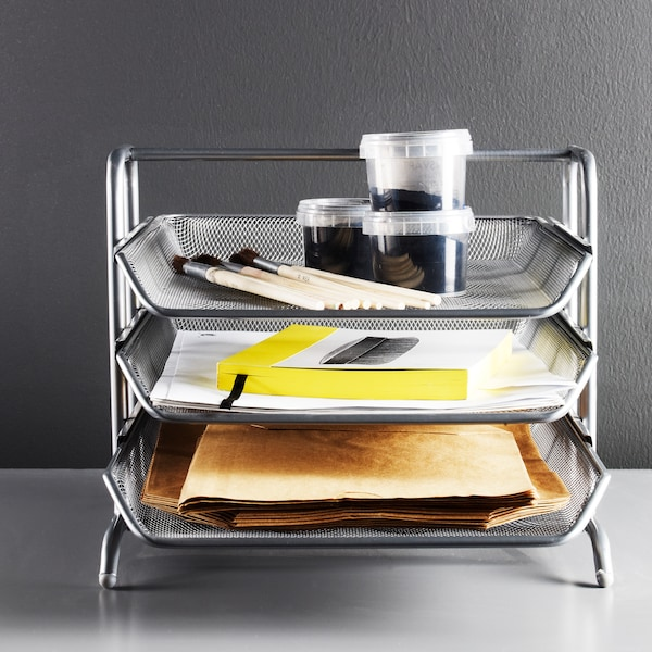 A metallic letter tray with three levels, holding plastic jars, files and various items placed on a white desk.