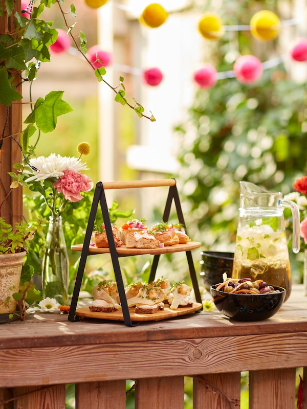 A FULLSPÄCKAD serving tray with canapés stands next to a jug and a bowl on a wooden surface in a blooming garden.