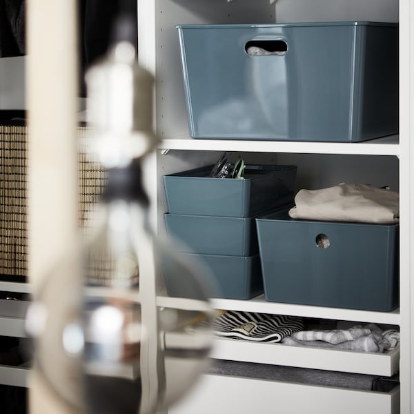 Different sized turquoise KUGGIS storage boxes with lids placed on white open shelves in the PAX wardrobe combination.