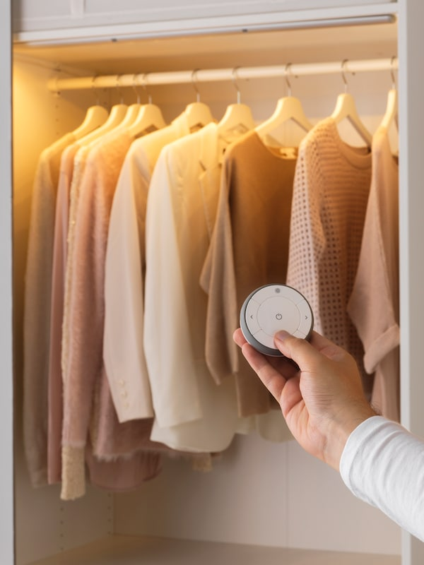 A hand holding a remote control, adjusting the smart lighting in a closet filled with clothes.
