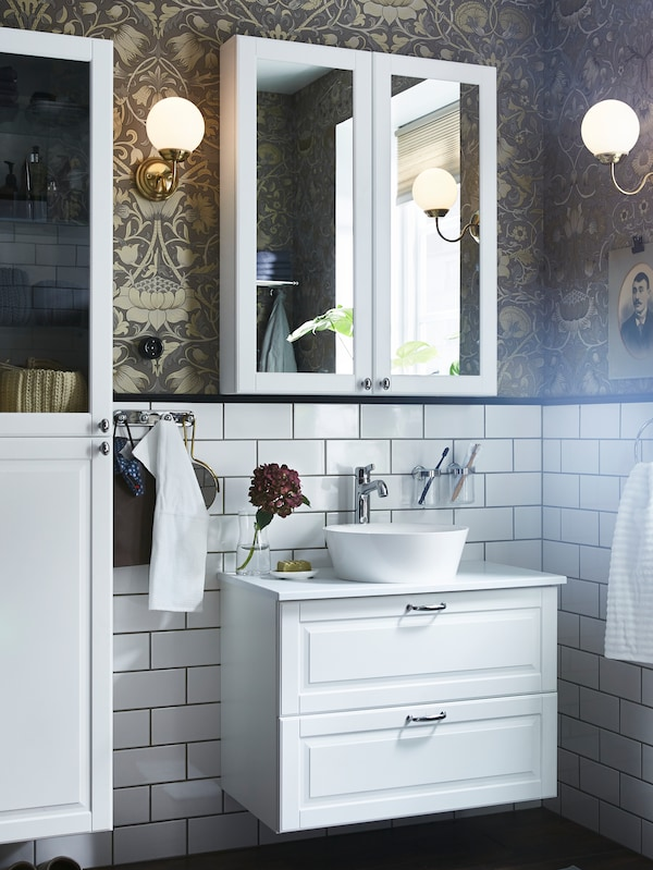 A mirror cabinet on a gold/brown wallpaper/white tiled wall, a white wash-stand with two drawers and a white high cabinet.