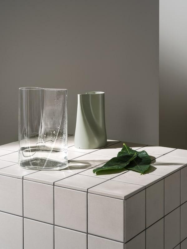 اثنانمن مزهرية/إبريقسقيCHILIFRUKTمن الزجاجالشفافوالفولاذالأخضرعلىجزيرة ببلاطاتبيضاء بجوار بعض الأوراق.