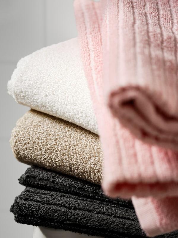 Harmaa, beige, valkoinen ja vaaleanpunainen VÄGSJÖN- kylpypyyhkee on pinottu päällekäin jakkaralle.