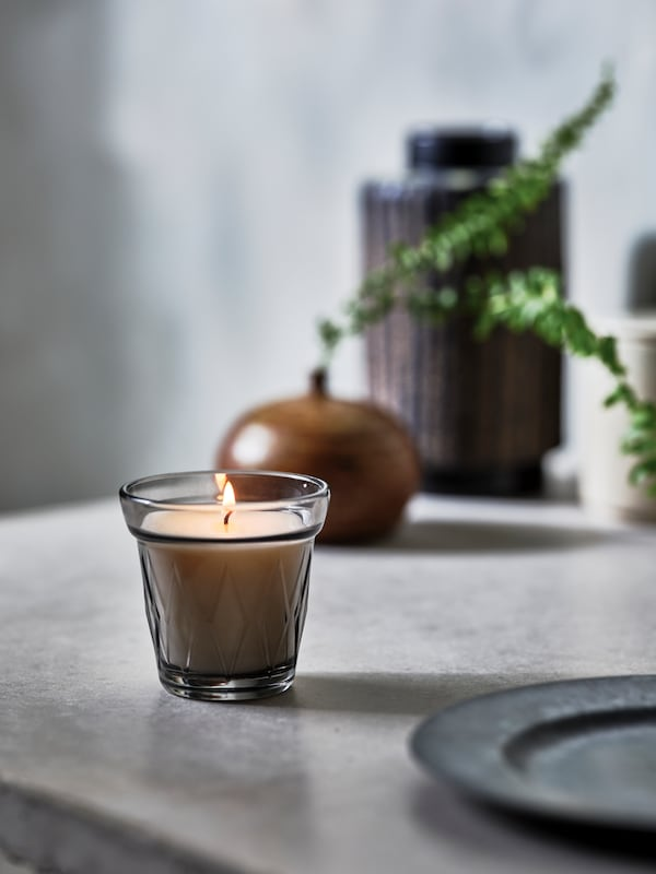 A lit VÄLDOFT scented candle in glass stands near a plate and a vase with a small plant in it and another vase.