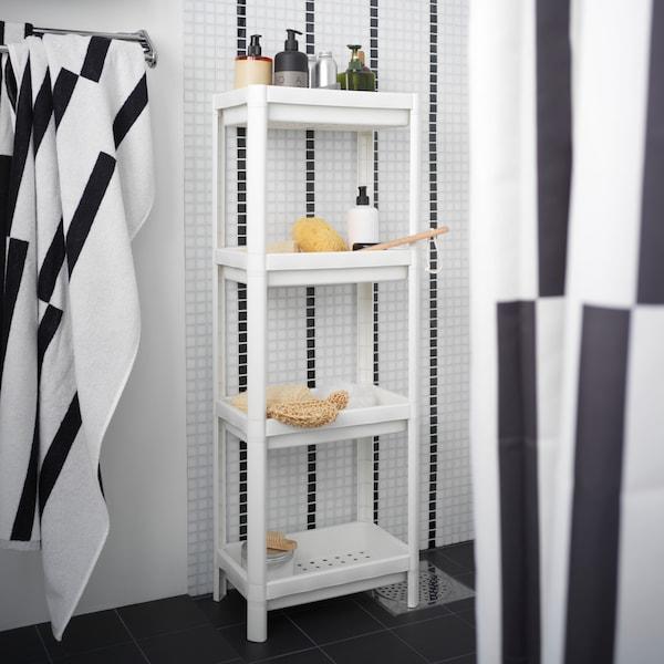 Valkoinen korkea hyllykkö, jossa pesusieniä ja shampoo pulloja. Mustavalkoinen pyyhe ja suihkuverho.