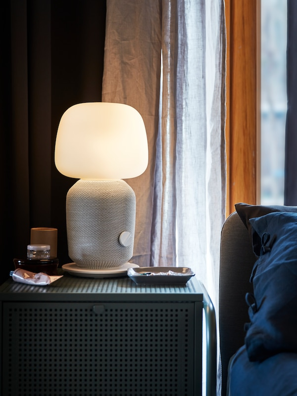 A nightstand with a white and grey SYMFONISK table lamp with a built-in WiFi speaker standing in front of a window.