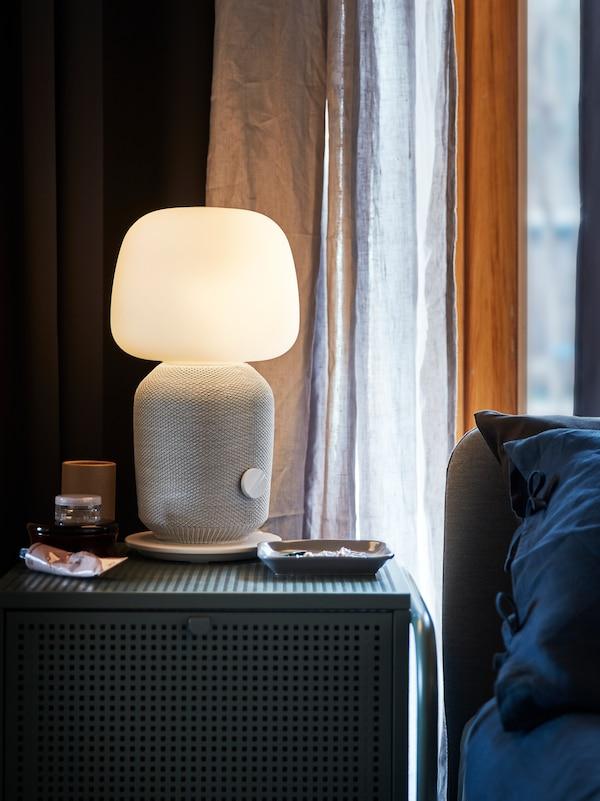 En hvid SYMFONISK lampe står på en NIKKEBY kommode. Bag ved er et vindue med lange gardiner og ved siden af kan man ane en seng.