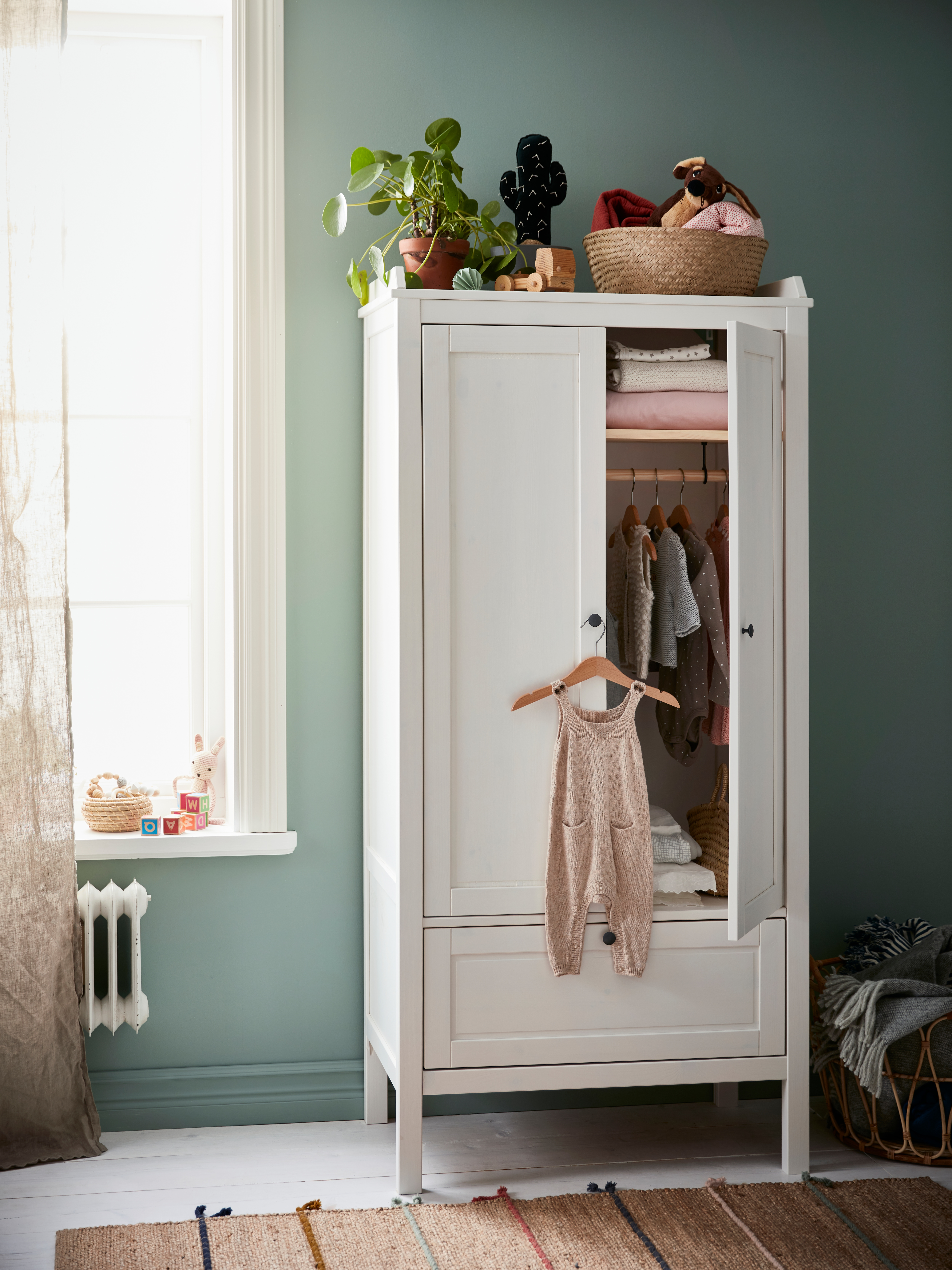 A white SUNDVIK wardrobe with a drawer and two hinged doors has a door open, showing baby clothes. It is on a green wall.