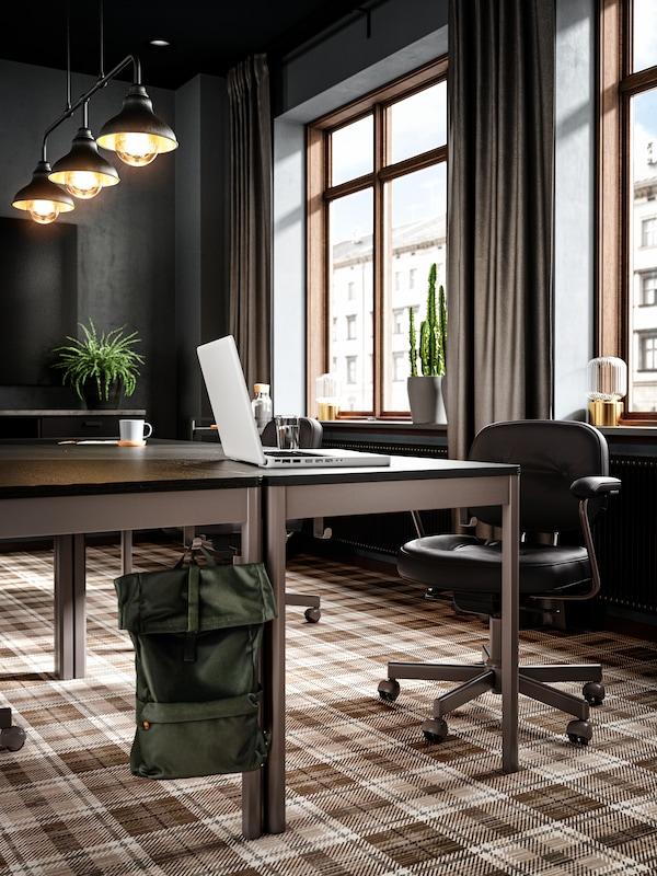 Tavoli accostati a formare un grande tavolo riunioni, sedie riunioni in pelle nera e un computer portatile bianco sul tavolo.