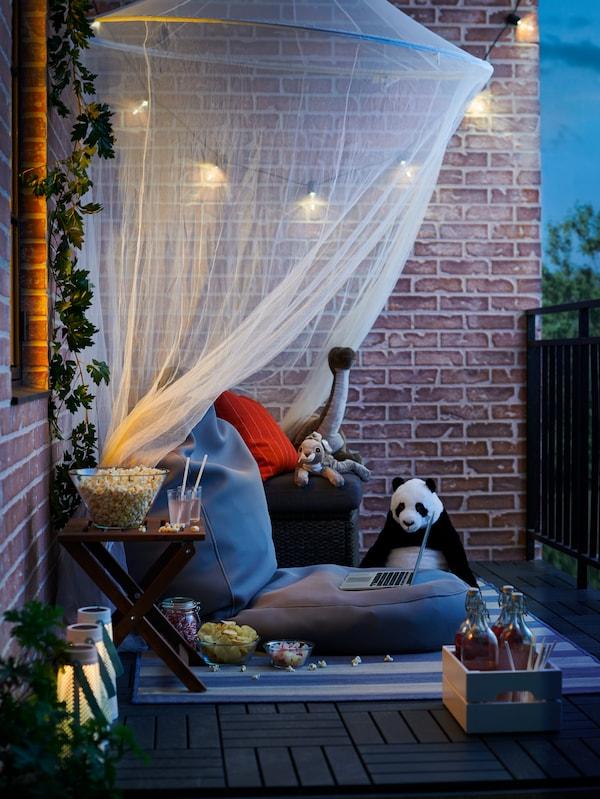 Un balcon dans la lumière du soir. Des lampes solaires sont allumées et éclairent un peu une moustiquaire que des poufs décorés de peluches.