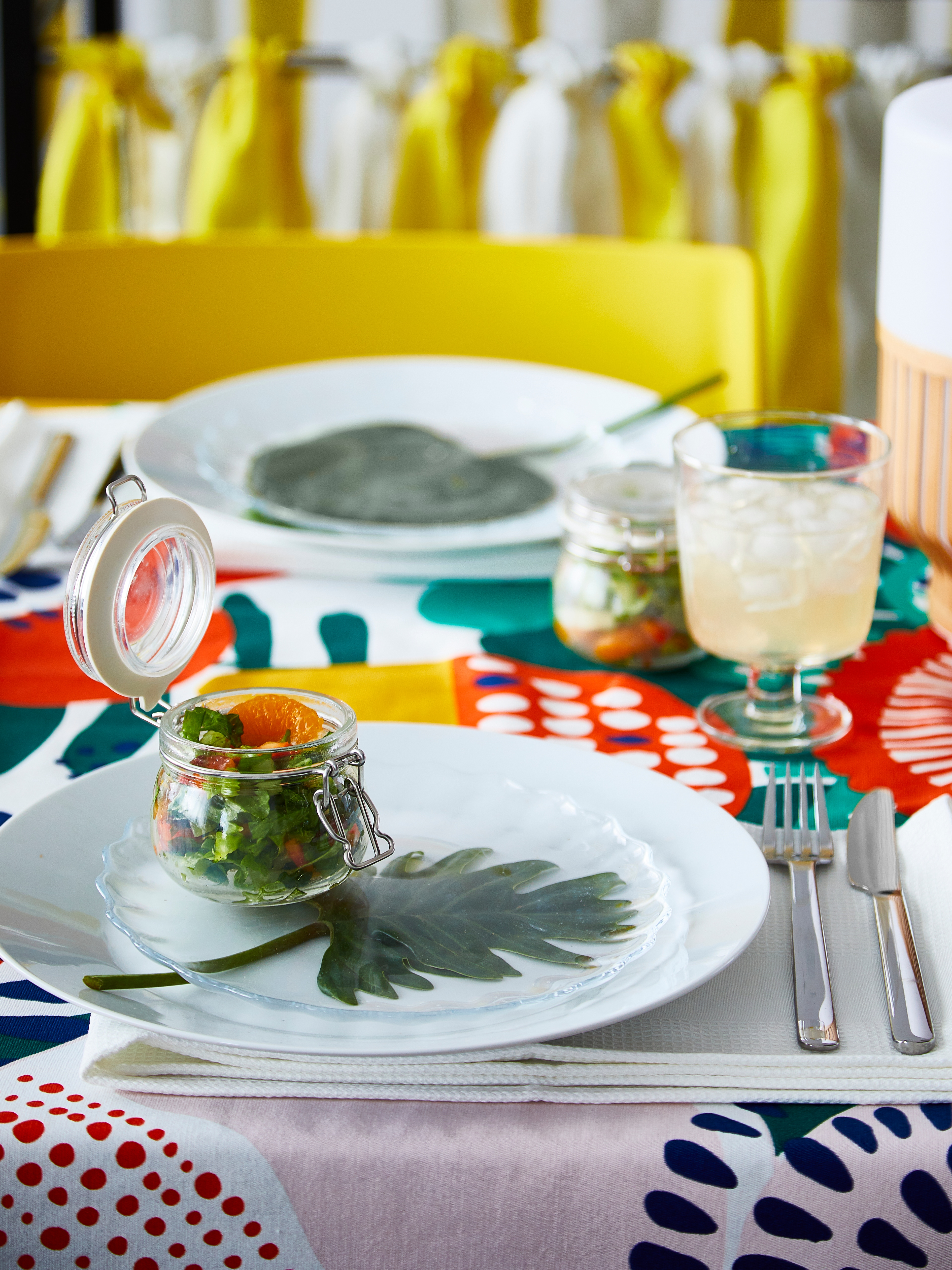 A place setting on brightly patterned table cloth with a drink in a glass and a salad in a clear glass KORKEN jar with lid.