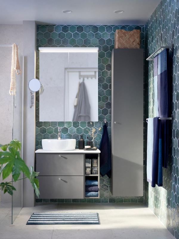Moderne bad med åttekantede fliser, grått servantskap, DALSKÄR blandebatteri og grått baderomsskap.