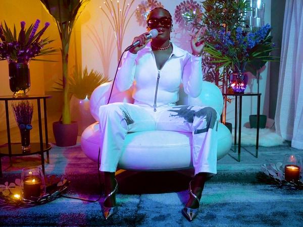 화이트 의상을 입고 화이트 색상 의자에 앉아 노래를 부르고 있는 뮤지션 아마레