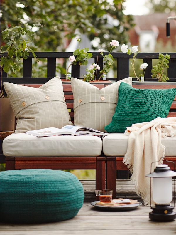 A sofa outdoors on balcony, with white and green cushions and a throw, a plate and a lamp on the floor.