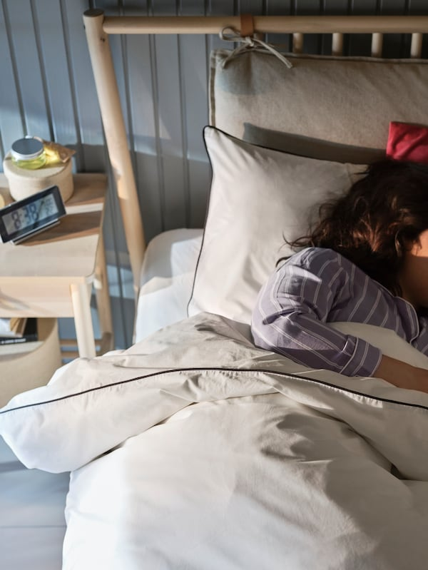 คนหลับอยู่บนเตียง BJÖRKSNÄS/บยอร์กสแนส ไม้เบิร์ชที่มีเครื่องนอน KUNGSBLOMMA/คุงส์บลุมม่า สีขาวหน้าผนังไม้สีเทาอมฟ้า
