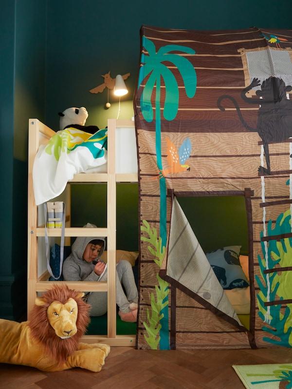 Un enfant est assis avec un livre dans un lit haut/bas KURA avec une tente de lit avec rideau KURA, à côté d'un lion DJUNGELSKOG.