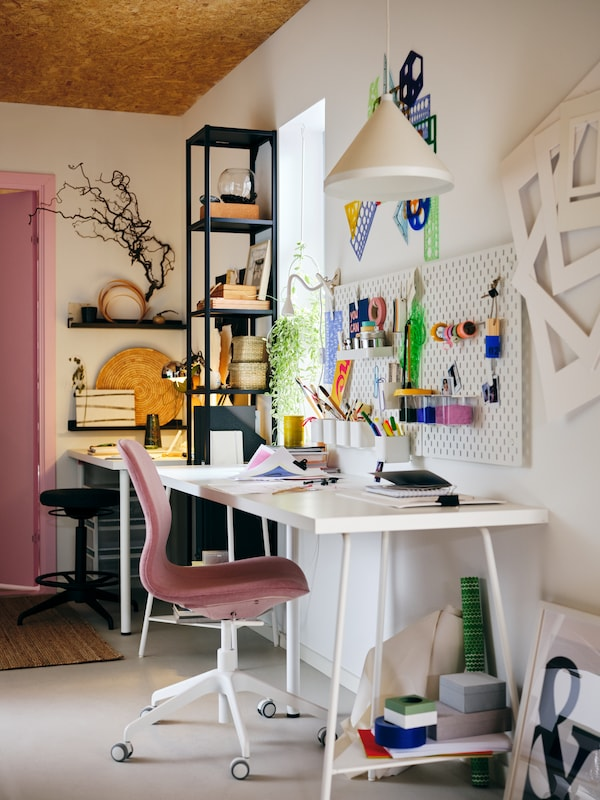 A colourfully decorated workspace centred around a white LAGKAPTEN tabletop and a pink LÅNGFJÄLL swivel chair.