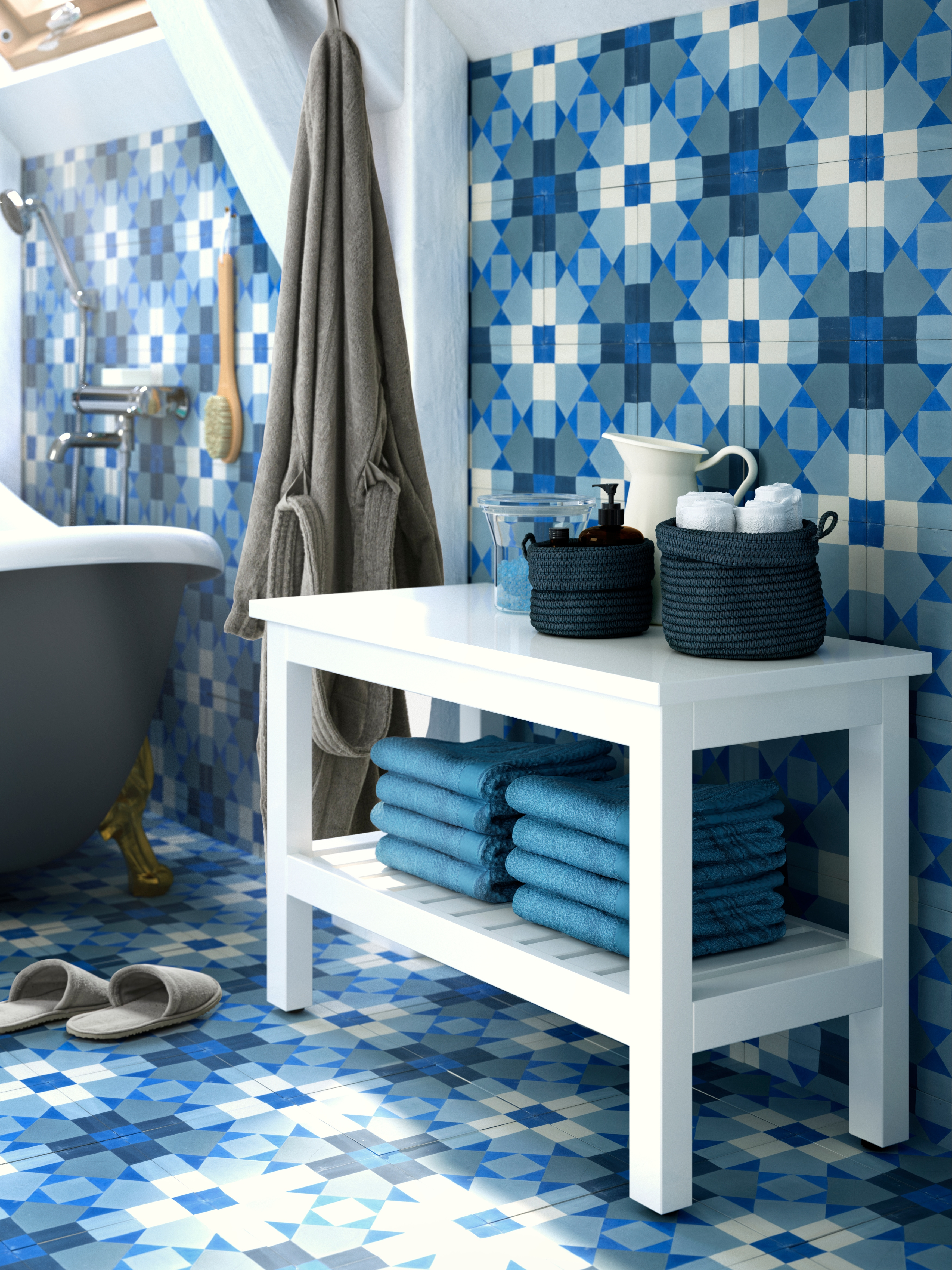 A tiled bathroom with a white HEMNES bench that has folded blue towels on the bottom shelf and small woven baskets on top.