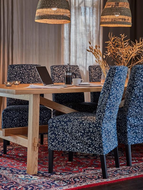 Une table en bois et des chaises revêtues de housses à motifs bleu foncé, un ordinateur portable, des bougies chauffe-plat et des suspensions tressées.