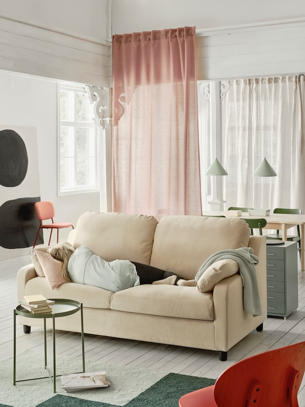 Living room with a sofa with a person taking a nap, a small tray table with books, and pink and white curtains behind.