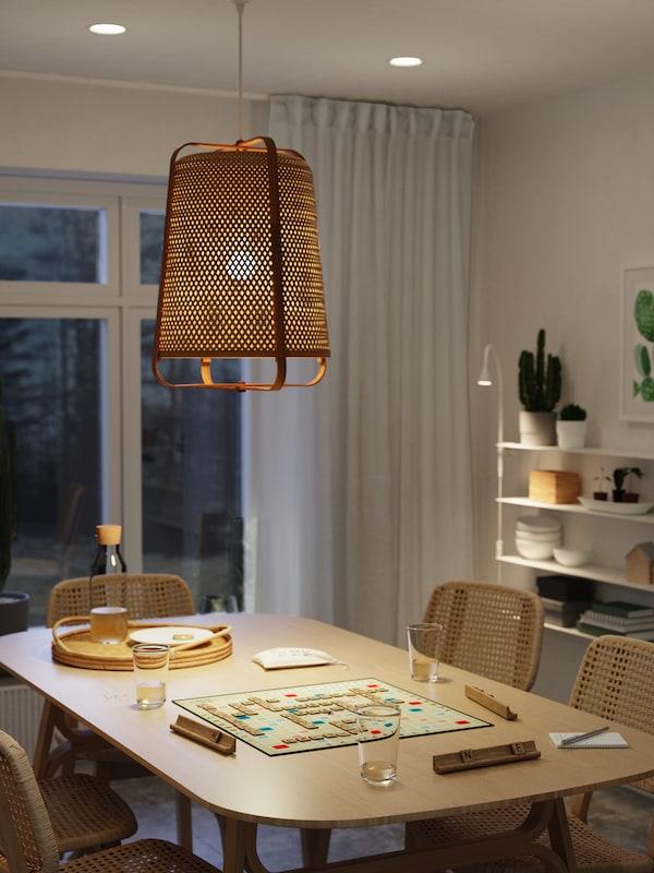 Spiseplass med bord og stoler av bambus og vevd papir, et brettspill og ei tent taklampe av bambus.