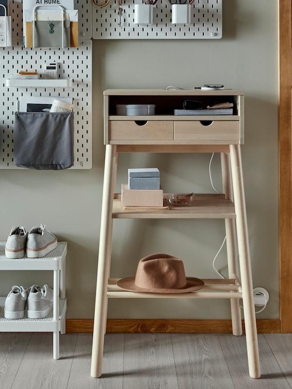 Un bureau debout KNOTTEN où sont rangés des livres, un chargeur et un chapeau, avec un tableau d'affichage au-dessus, près d'un range-chaussures MACKAPÄR où sont posées des chaussures.