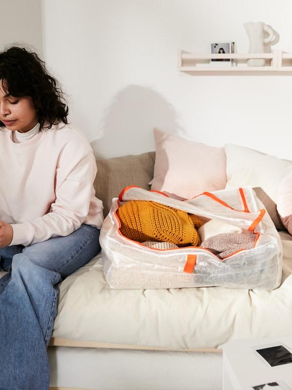 Une jeune femme assise sur un lit à côté d'une boîte-tiroir blanche PÄRKLA avec des détails orange, remplie de vêtements.