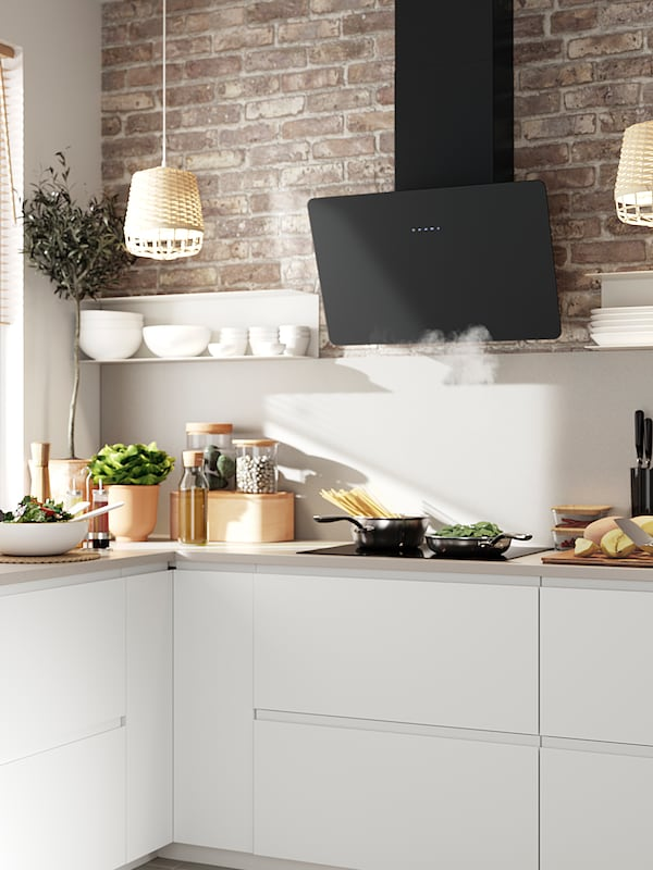 A kitchen with white cabinets, a black extractor and an exposed brick wall. A pot and a pan with food in is on the hob.