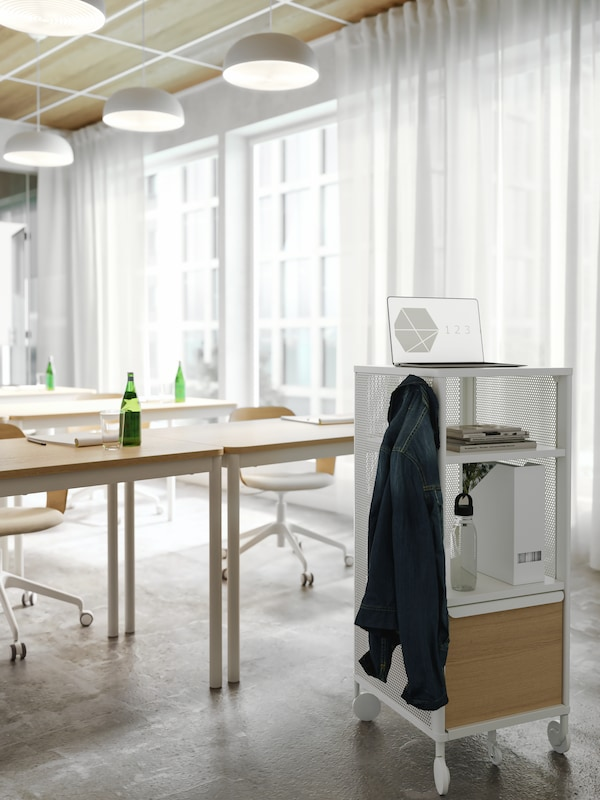 A white storage unit on castors used as a presentation stand in a conference room. A jacket hangs on a hook on its side.