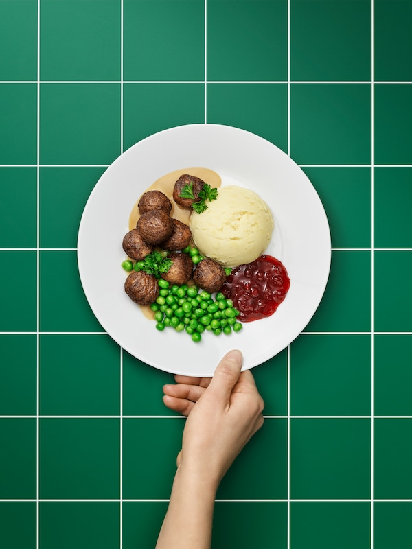 A hand reaching out to serve a meal of consisting of Plant balls, fresh peas and mashed potatoes, on a round white plate.