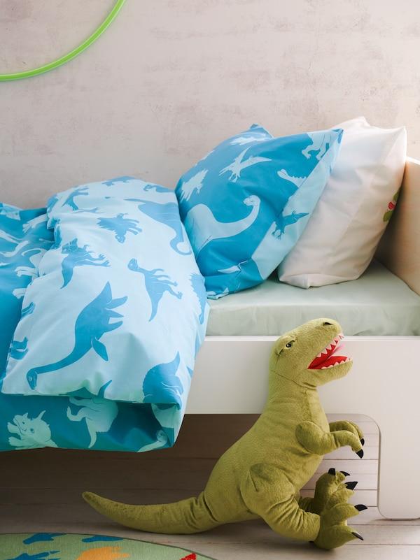 En mjukleksak i form av en dinosaurie och en barnsäng bäddad med ett blått JÄTTELIK påslakan och örngott med dinosauriemönster.