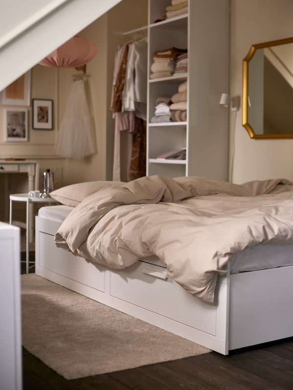 An extended white BRIMNES daybed made with light gray/beige bedlinen, with a white shelving unit and a gold-color framed mirror.