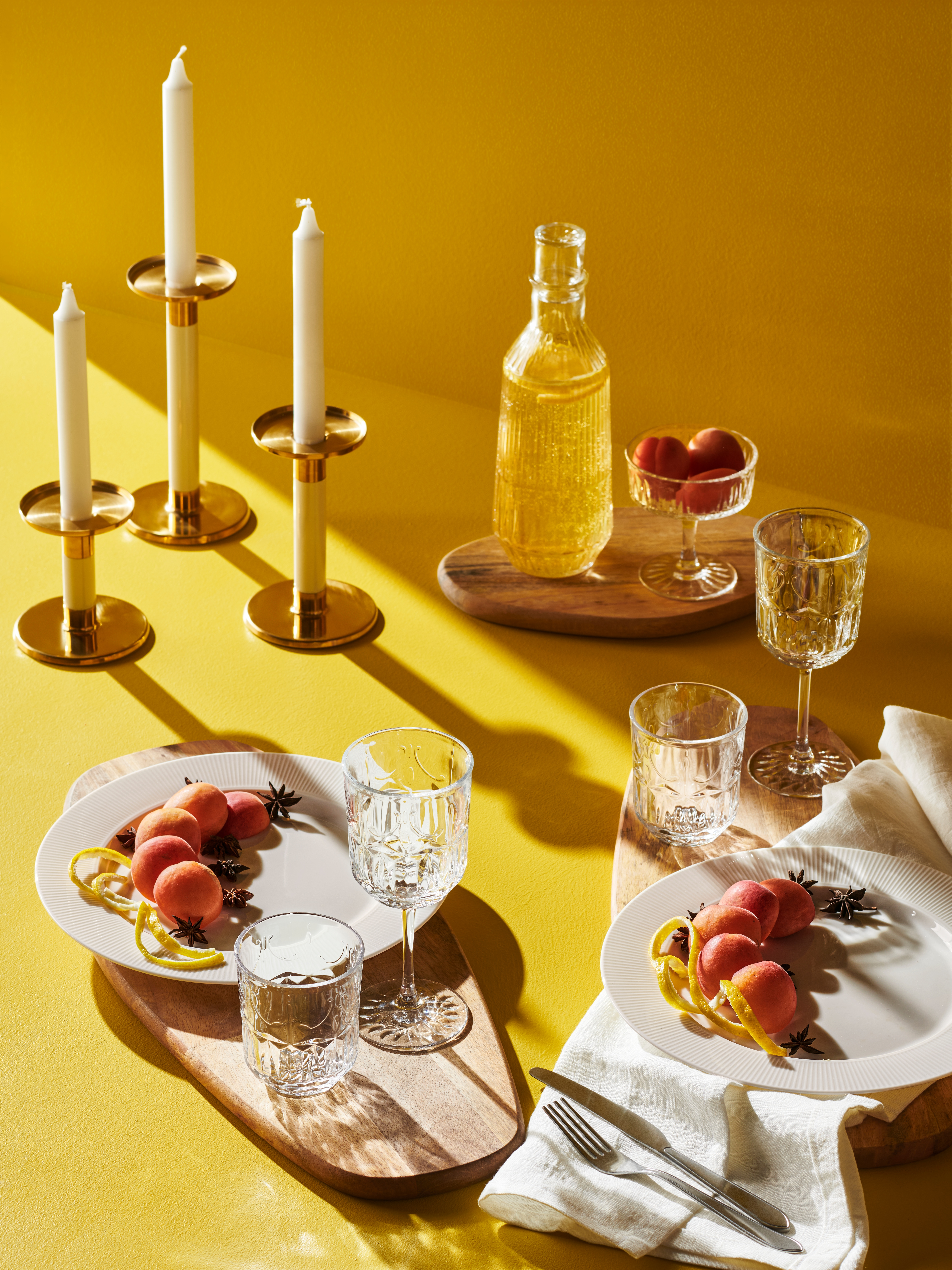 SÄLLSKAPLIG cut glasses and carafe on wooden boards on a yellow surface with peaches on plates and candles in gold holders.