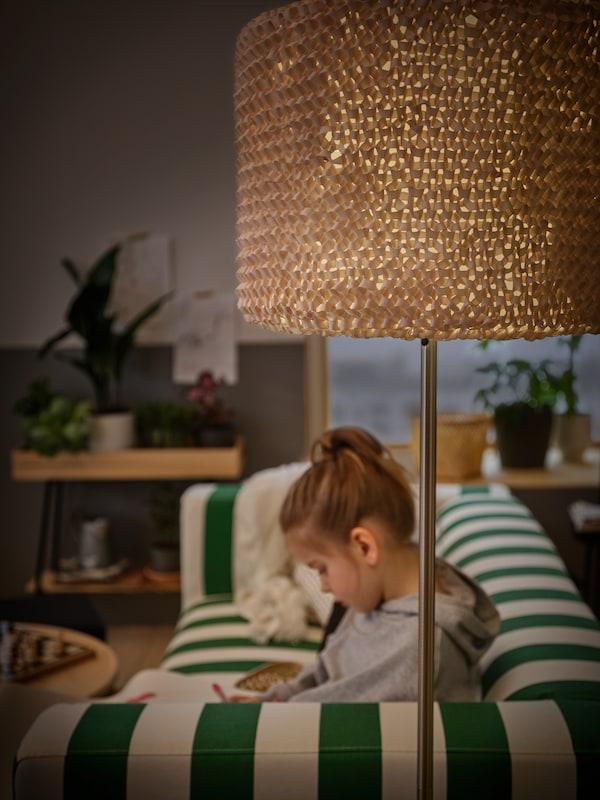 Une petite fille sur un canapé KLIPPAN est en train de dessiner de façon concentrée. On peut voir un lampadaire SKAFTET avec un abat-jour LERGRYN devant le canapé.