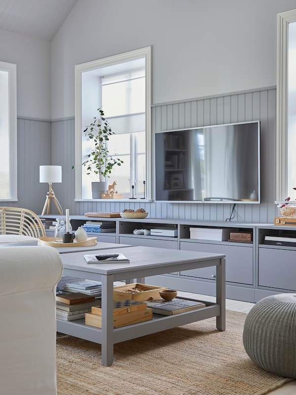 Bright, grey toned living room. Jute rug on floor with grey HAVSTA coffee table in center of the room. TV mounted on wall, grey TV unit underneath