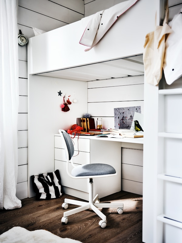An ÖRFJÄLL chair in front of a white desk that's under a SMÅSTAD loft bed in a white bedroom with a dark wood floor.