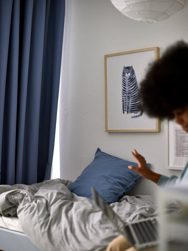A woman with a computer on a bed with light grey bed linen, with a blue BENGTA block-out curtain by the foot of the bed.