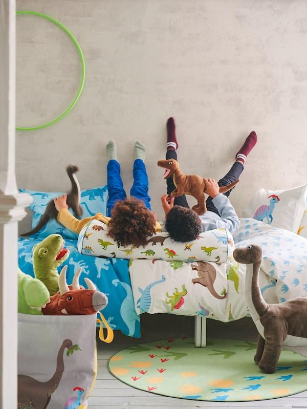 Två barn ligger på en säng med benen på väggen och vilar huvudet på en kudde tillsammans med sina gosedjur